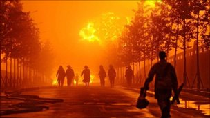 Firefighters walk near the scene of the blaze after the oil pipeline blast site in Dalian in north east Chin's Liaoning province