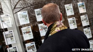 Man looking in an estate agent's window