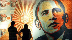 Two people look at the mural of Barack Obama by Shepard Fairey.
