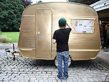 image of one of the artists spraying the caravan gold
