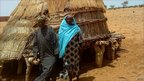 Nigerien farmer Seydou Boubacar, 40, and his wife, Zaina, standing in front of their full grain silo in Bokki village south-east of the capital, Niamey © ICRISAT