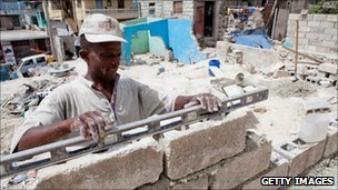Man rebuilds a home in Port-au-Prince (12 July 2010)
