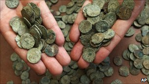 British Museum staff member displays a handful of the coins of the Frome Hoard