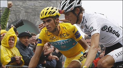 Andy Schleck puts an arm around Alberto Contador as they cross the line together at the top of the Tourmalet