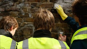 People scrubbing graffiti from a wall
