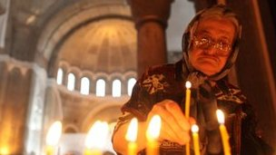 A woman lights candles at St. Sava temple during mass prayers for Kosovo in Belgrade July 22, 2010