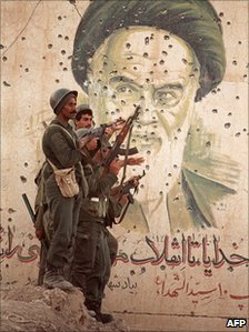 Iraqi soldiers pose by a bullet-riddled portrait of Iranian leader Ayatollah Khomeini on Iran's Faw Peninsula during the war, April 1988
