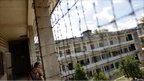 A woman looks through wire fencing into the courtyard of Tuol Sleng prison