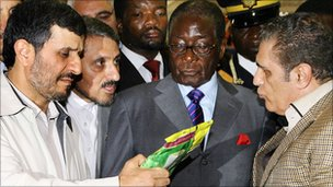 Mahmoud Ahmadinejad (l) and Robert Mugabe (c) inspect produce at a trade fair