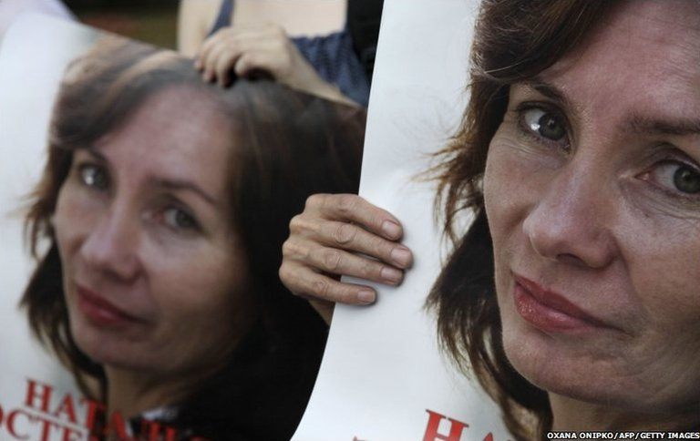 Russian activists hold portraits of slain human rights activist Natalya Estemirova