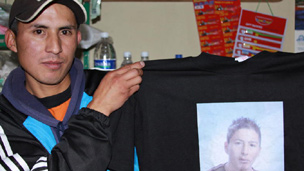 Carlos Olivo holds a T-shirt imprinted with his brother's picture
