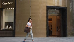 Woman walks past Cartier shop in Shanghai