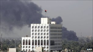 Smoke billows from the al-Arabiya office in central Baghdad, 26 July