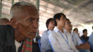 Elderly man watches the verdict with school-age children in Phnom Penh