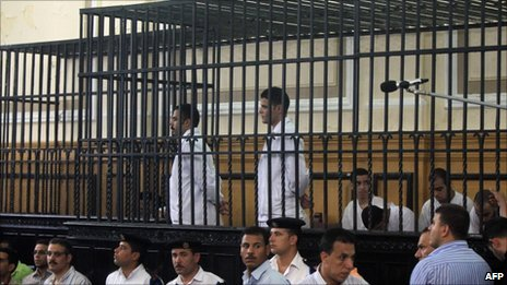Defendants Salah and Suleiman stand in cages as they attend their first court hearing.