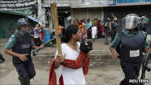 A garment worker holds a wooden stick during a protest in Dhaka in June 2010