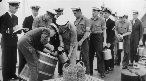 Sailors are issued with their rum ration on the HMS Torquay, circa 1956