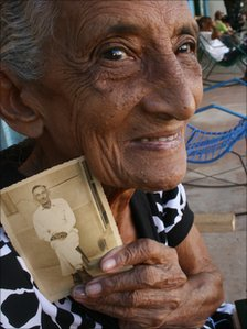 Woman holds a photo of a family member from the time of the move to the Amazon