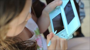 Girl playing on a Nintendo DS Lite Handheld computer games