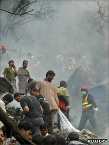 Rescue workers search the site of the crash of an Airblue passenger plane on the outskirts of Islamabad