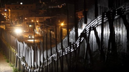 Traffic moves along the border fence separating Nogales, Ariz., and Nogales, Sonora, Mexico, Tuesday, July 27, 2010.