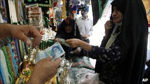 A woman uses Iranian rials to pay for goods at a market stall in Karbala, July