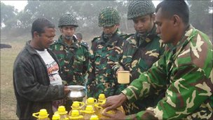 Soldiers distributing Soya bin Oil