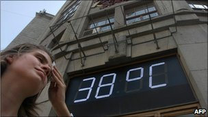 A Russian woman wipes her forehead under a temperatre sign reading 38C (100F) in Moscow, 29 July 2010