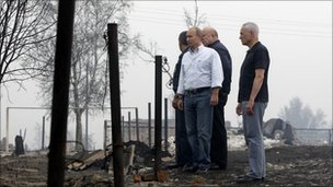 Vladimir Putin and officials visiting fire damaged village