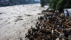 Pakistani residents stand by flood water that entered a residential area of Muzaffarabad on July 30, 2010.