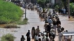 Pakistani flood victims pass through Nowshera district, 31 July