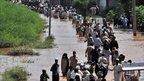 Pakistani flood victims pass through Nowshera district, 31 July