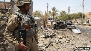 An Iraqi soldier stands guard at the site of a bomb attack in Baghdad, 26 July 2010 