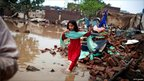 A girl runs through the courtyard of her flood-affected family home