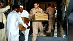 US crew members hand over relief packages to local officials for flood affected people at Peshawar airport in Pakistan