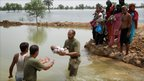 Pakistan army soldiers pass a baby across water in Taunsa, near Multan, as villagers look on