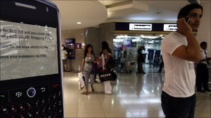 A man speaks on his mobile phone as he stands next to a display of a BlackBerry at a shopping mall in Dubai