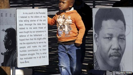 A boy stands next to a picture of former South African President Nelson Mandela at a museum in Mvezo during Mandela's 92nd birthday celebrations, about 70km from Mthatha, in the Eastern Cape