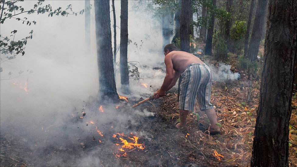 Man putting out fire with sticks. Photo: Ilya Varlamov (zyalt)