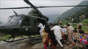 Pakistani flood survivors rush towards an army helicopter near Medain, Pakistan (August 2, 2010).