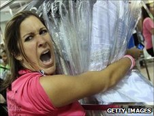 Bride-to-be Nicole Christos holds a rack of a wedding gowns during Filene's Basement's annual sale in Bethesda, Maryland