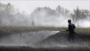 A Russian firefighter works to extinguish dry grass burning near the town of Voronezh, 500 km (294 miles) south of Moscow