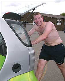 Adrian Kane pushing a Smart car