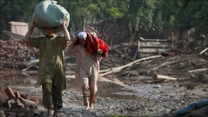 "Family members salvage belongings from their destroyed house in Pabbi, located in Pakistan""s northwest Khyber-Pakhtunkhwa"