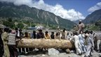 People push a log to make a temporary bridge over the Swat river