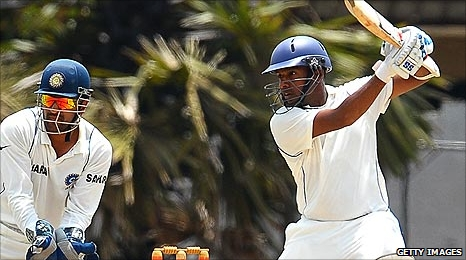 Thilan Samaraweera plays a stroke while watched by Indian captain Mahendra Dhoni