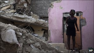 A woman stands in the remains of her home on 5 August, 2010
