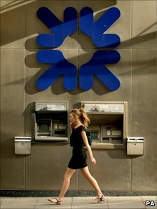 Woman walks past an RBS branch