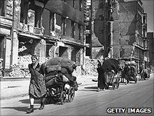 Berliners pull carts through bombed streets in 1945