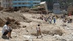 Residents of Zhouqu, in Gansu, inspect fallen buildings